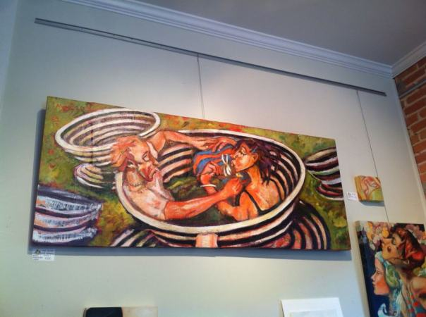 "Love Spirals - Isn't Spinning Grand? Shown on display at Lantana's Gallery in Southport, North Carolina. (available) 50""wx24""h, Figure on left is holding up buttercup to woman's chin to see if she is favored by love. Woman holds a daisy with petals of ""he loves me"" and ""he loves me not. A self portrait of the artist with the flow artist and juggler Sebastian Gomez."